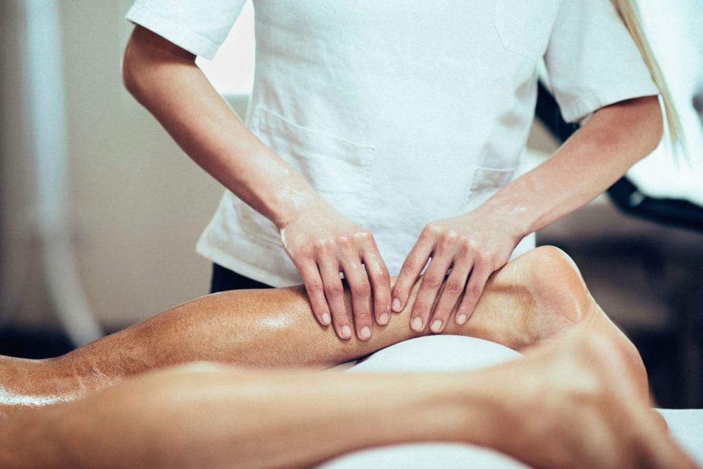 a massage therapist massages a patient's ankle and calf at Summit Chiropractic & Sports Institute