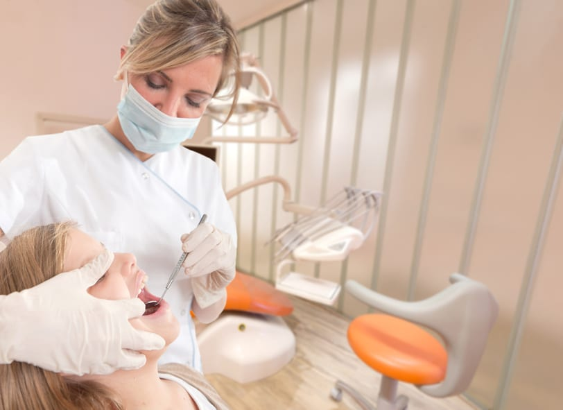 A dentist holding a mirror in a young patient's mouth