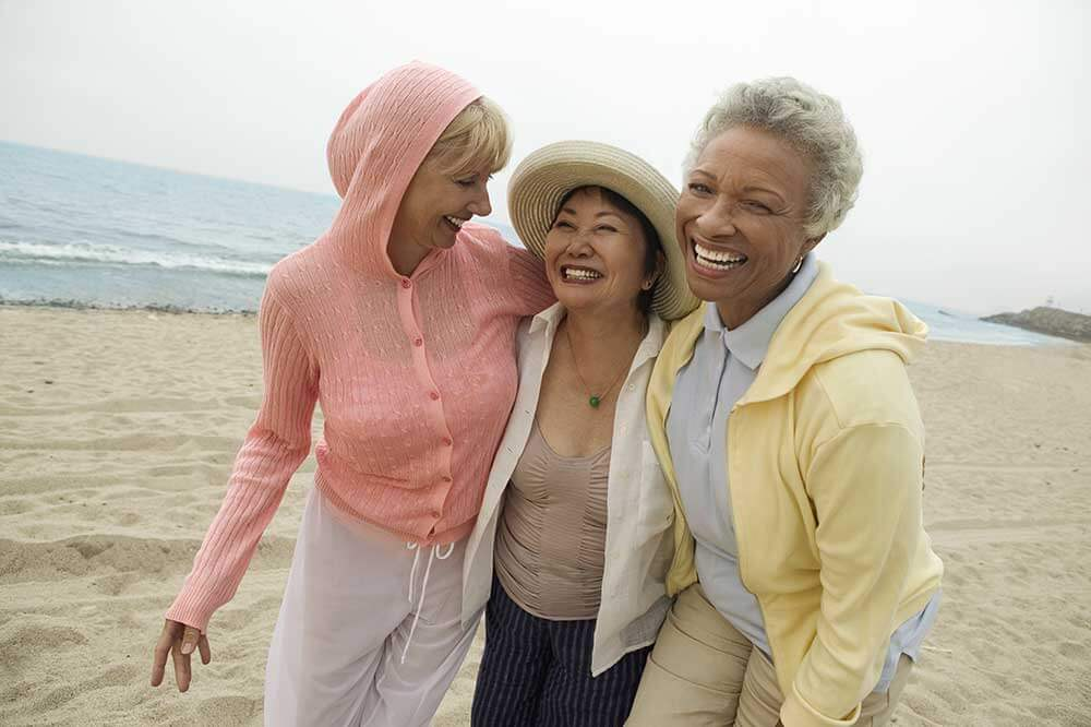 Three smiling older women walking on the beach with their arms around each others shoulders