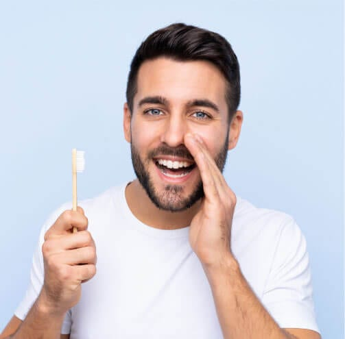 A man with dark hair holding a toothbrush in one hand and holding his other hand up as if whispering