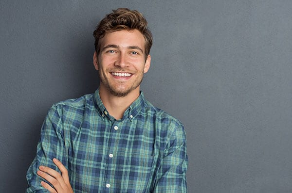 A smiling man in a blue plaid shirt standing against a dark gray background