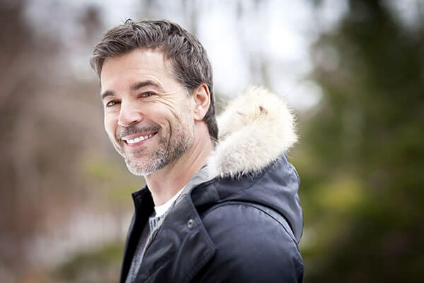 A smiling man wearing a fur lined winter coat with trees blurred in the background
