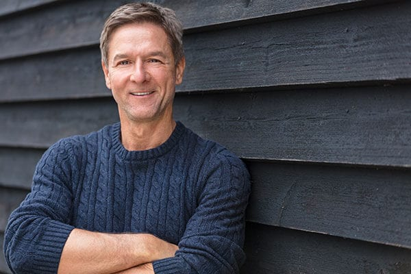 A middle aged man wearing a dark blue sweater leaning against a dark gray wood wall