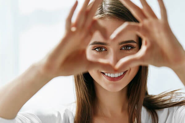 Smiling woman holding fingers up in heart shape to frame her eyes