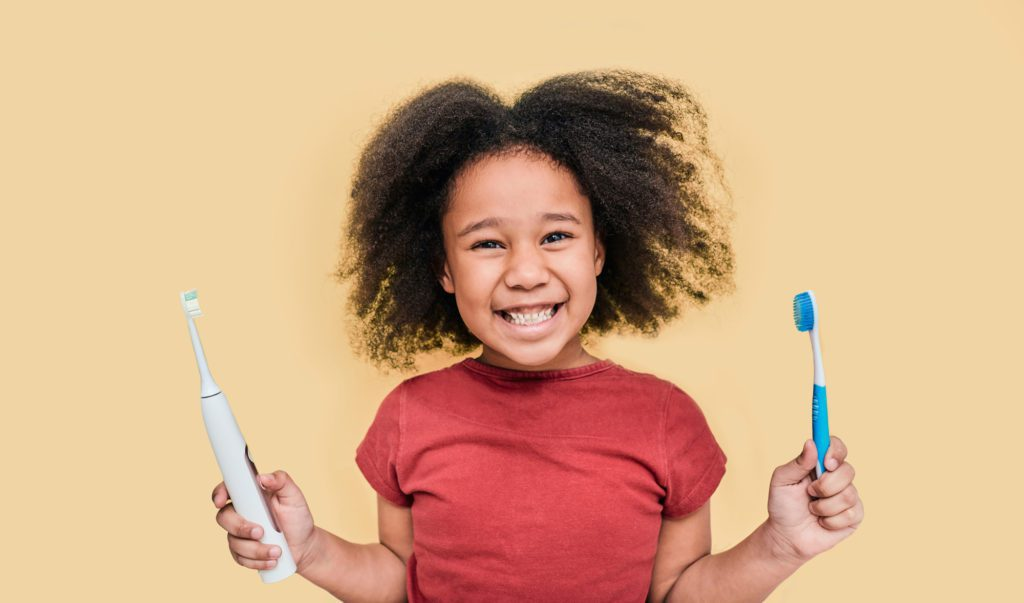 Young female patient at Summit Family and Cosmetic Dentistry chooses between an electric toothbrush and a manual toothbrush.